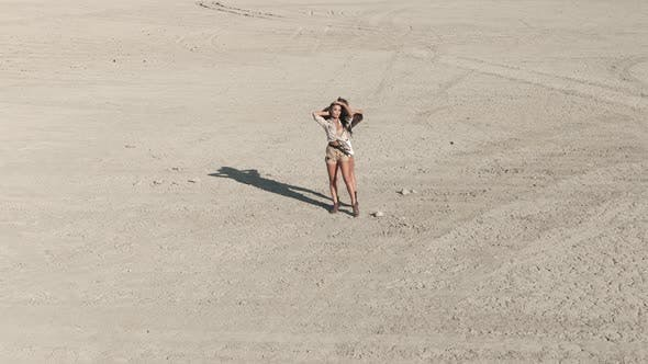 Cover Image for AERIAL Shot Two Young Women Is Standing in the Middle of the Desert They Rising Up Their Hands and