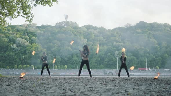 Cover Image for Young Slim Man and Two Beautiful Women Simultaneously Perform Show with Flame While Standing