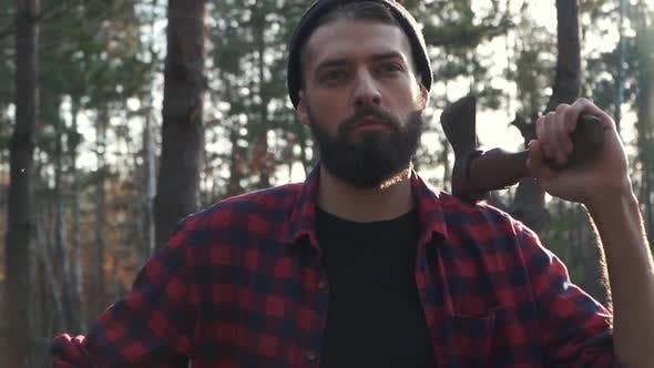 Thumbnail for Portrait of a Bearded Man in a Plaid Shirt Standing with an Ax in His Hand in the Forest