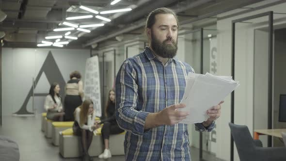 Cover Image for Concentrated Bearded Man Studying Papers Documents Standing in the Office