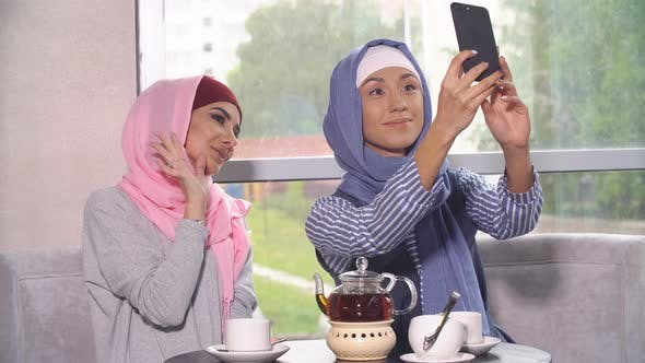 Thumbnail for Two Young Women in Hijabs Do Selfie on a Smartphone. Muslim Women in a Cafe