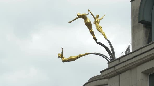 Golden gymnasts statues on a building