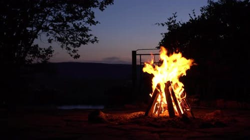 A Bonfire Burns in the Middle of the Night. Fire on the Background of the River and Mountains.