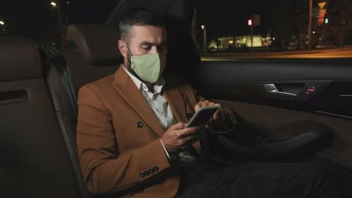 Businessman In Mask At Backseat