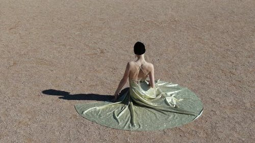 A Young Woman in an Evening Dress Sits on a Sand Art Deco Woman Ar Nuvo Fashon