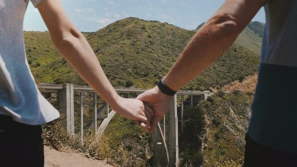 Cover Image for Close-up Man and Woman Walk Together Holding Hands at Epic Beautiful View of Bixby Creek Bridge