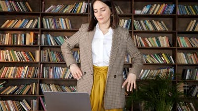 Tired Businesswoman in Yellow Skirt Stands Up and Stretches