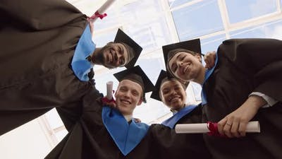 Four Happy Diverse Friends with Diplomas during Graduation