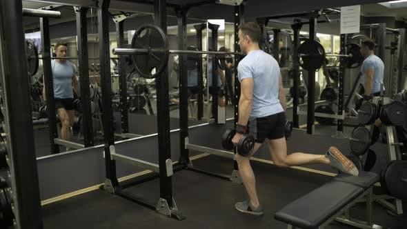 Thumbnail for Attractive man doing lunges step-ups with heavy dumbbell.