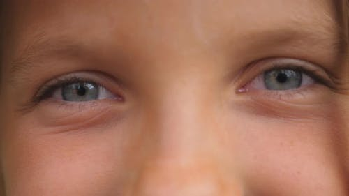 Close Up of Blue Eyes of Happy Small Girl Blinking and Looking Into Camera with a Happy Sight