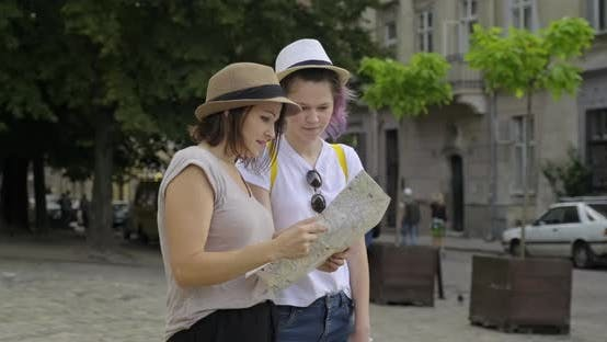 Cover Image for Mother and Teenage Daughter in Old Tourist City with Map