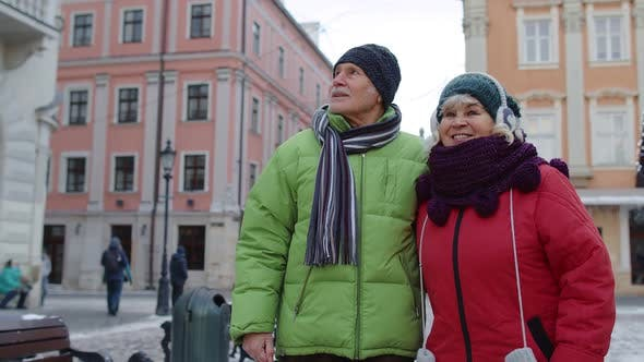 Stylish Happy Senior Couple Tourists Grandmother Grandfather Walking Traveling in Witer City Center