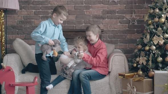 Fair haired Geschwister versuchen, Spielzeug in einen dekorativen Käfig zu stecken