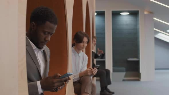 Three Young Businesspeople Using Smartphones