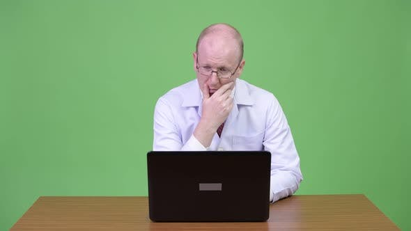 Thumbnail for Mature Bald Man Doctor Thinking While Using Laptop Against Wooden Table