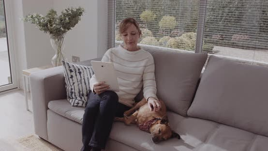 Mature adult female sitting with dog on sofa looking at digital tablet