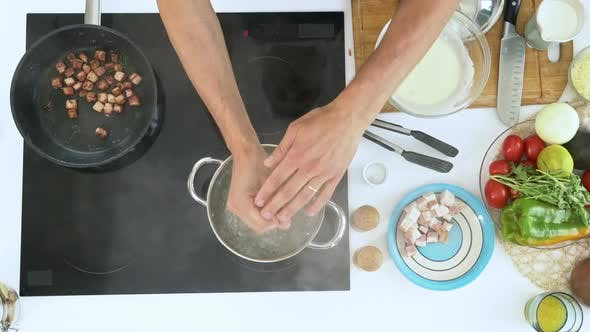 Thumbnail for Man Putting Spaghetti into Boiling Water