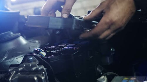 Male Mechanic Checking and Repair the Engine in Car Service