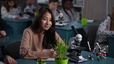 Smiling Asian Schoolgirl Posing on Camera at Desk