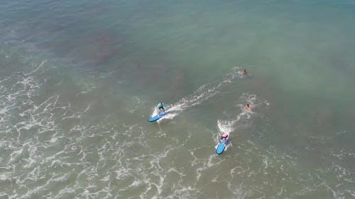 Two Beginners Surfing In Ocean Surf School. People Surfing in the Ocean of a Beautiful Beach Bali