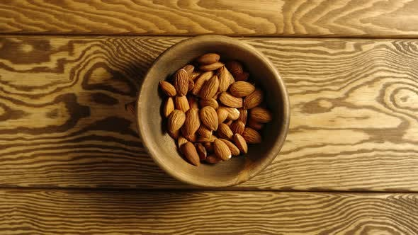 Thumbnail for Almond Kernels Fall Into A Wooden Dish On A Table