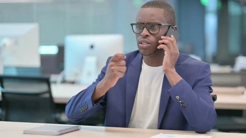 African Businessman with Laptop Talking on Smartphone