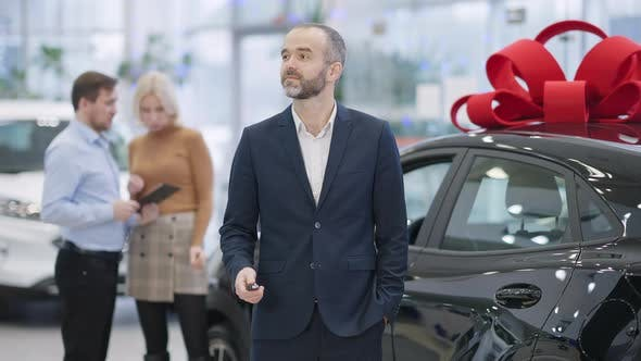 Satisfied Caucasian Businessman Standing with Car Keys at Black Luxurious Vehicle in Showroom with