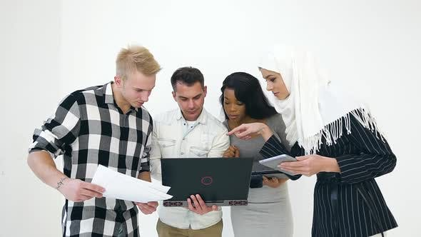 Cover Image for Serious Multiethnic Agreeable Office Workers Looking at the Computer and Discussing Project Details