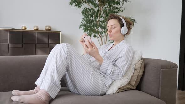 Thumbnail for Girl Listening Music Wearing Headphones On Sofa Using Smartphone
