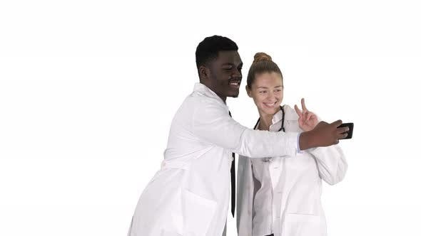 Thumbnail for Two Doctors Are Making Selfie Using a Smartphone and Smiling on White Background.