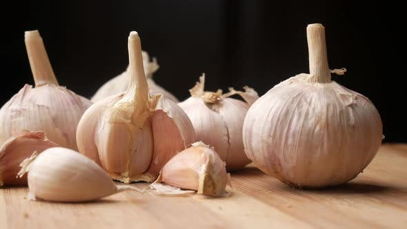 Close Up Pf Garlic on a Chopping Board Against Black Background