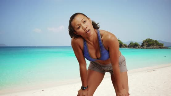 Thumbnail for Toned Filipino woman jogging on the beach checking fitness tracker