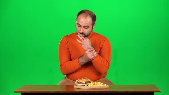Caucasian Man with Overweight Looks at Delicious Junk Foods on the Table and Resisting Unhealthy