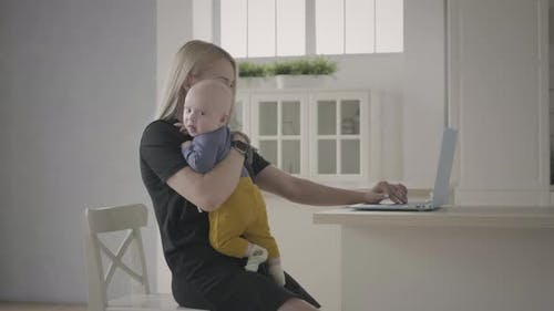 Mother Working At Home Hodling Toddler