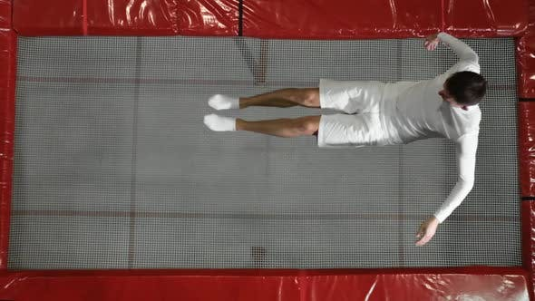 Thumbnail for The View From the Top Gymnast Acrobat Dressed in White Performs a Somersault on the Trampoline