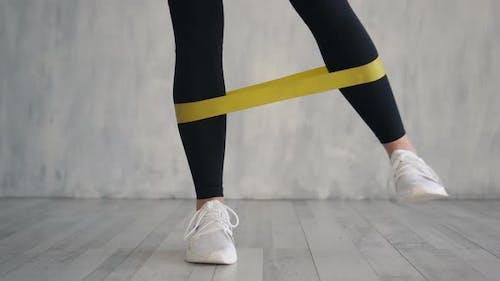 Weibliche Übung Fitness elastisches widerstandsfähiges Band, Nahaufnahme der Beine