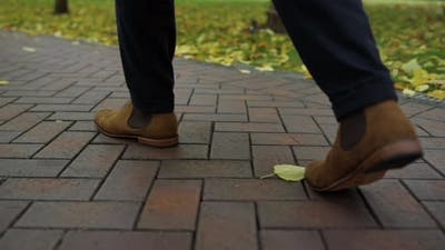 Unrecognizable Man Feet Strolling on Street