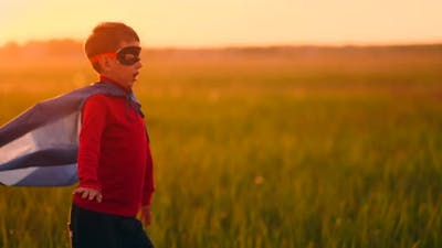 A Boy in a Superhero Costume at Sunset Runs Across the Field Laughing and Smiling