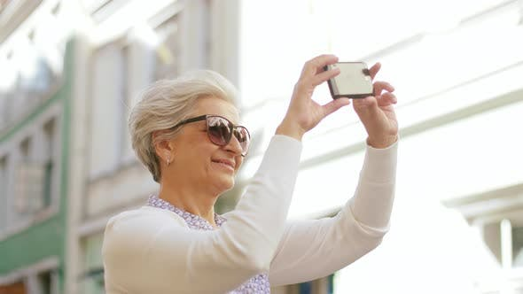 Thumbnail for Senior Woman Photographing By Smartphone in City