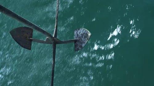 Anchor of Moving Motorboat Swinging Above Shining and Splashing Ocean Water.