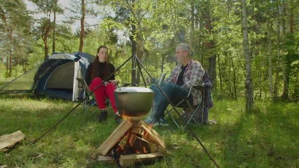 Tourist Couple on Camping Trip Drinking Hot Drink Near Campfire