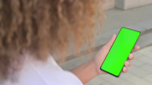 African Woman Holding Smartphone with Green Chroma Screen