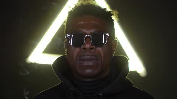 Thumbnail for African Man in Sunglasses Smoking on Dark Studio