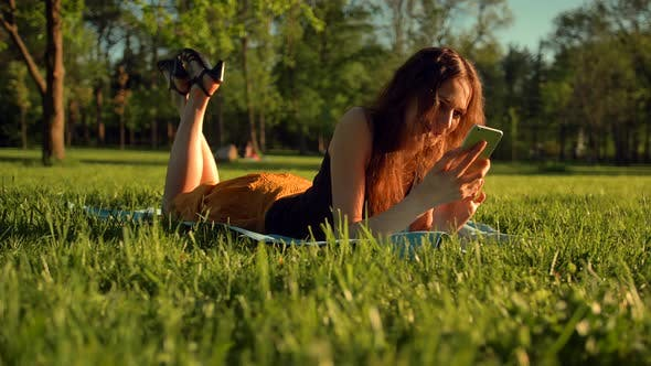 Thumbnail for Happy Female Types Sms or Chat, Sitting in Park on Grass. Woman Chatting in Telephone.