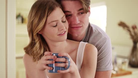 Thumbnail for Joyful male hugging girlfriend with coffee mug from behind inside small kitchen