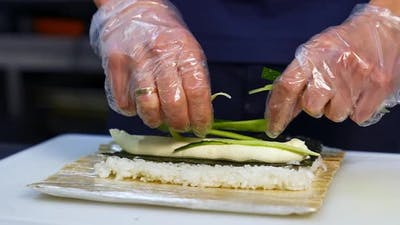 Hands cooking sushi with rice. Close up of chef hands preparing japanese food