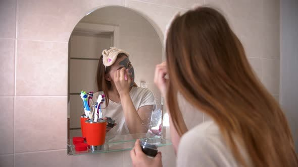 Thumbnail for A Young Woman Applying a Grey Face Mask on Her Face Using a Brush