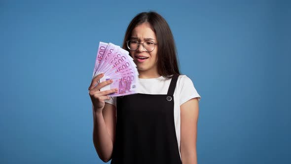 Thumbnail for Satisfied Happy Excited Asian Girl Showing Money - Euro Currency Banknotes on Blue Wall.