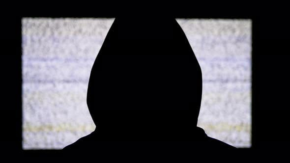 Thumbnail for Silhouette of Man's Head in Hood Is Watching White Static Noise and TV Interference.