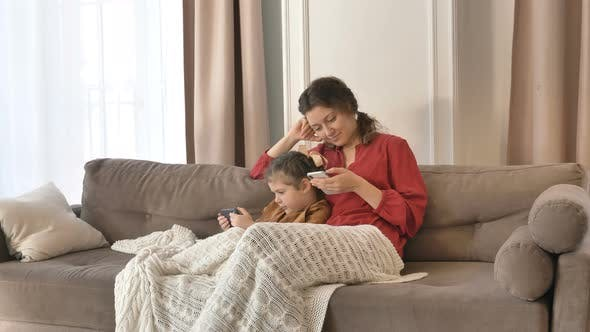 Cover Image for Mom and Daughter Spend Time at Home with Their Phones in Their Hands, Make Online Purchases and Chat